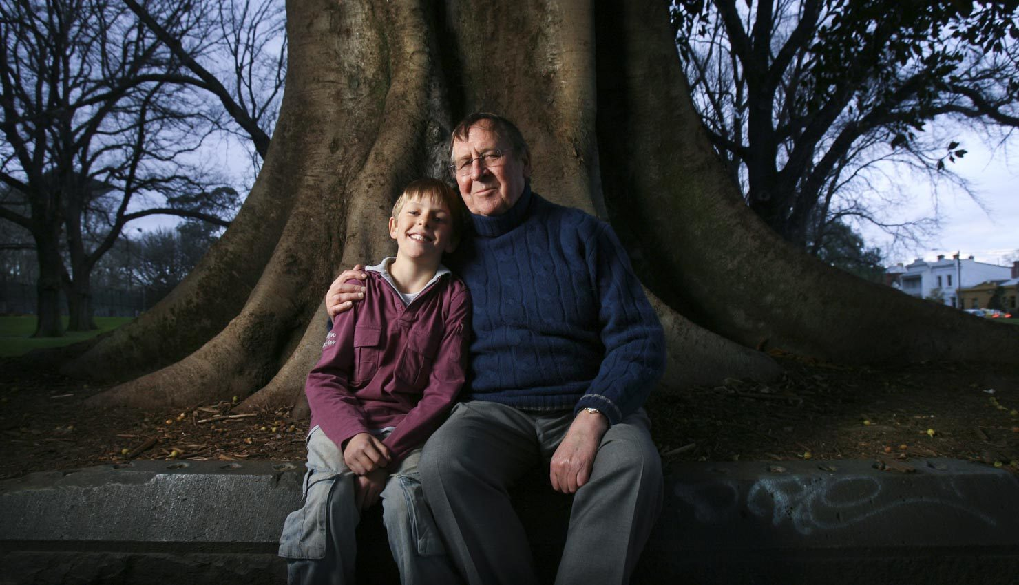 A father & son in front of a large oak tree