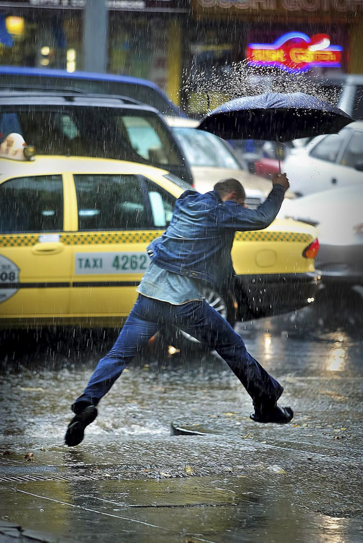 Man jumps a puddle in pooring rain with a taxi behind
