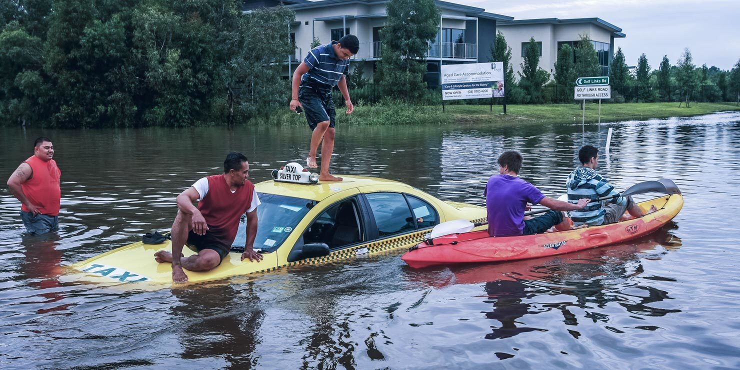People standing on a taxi in the middle of floods