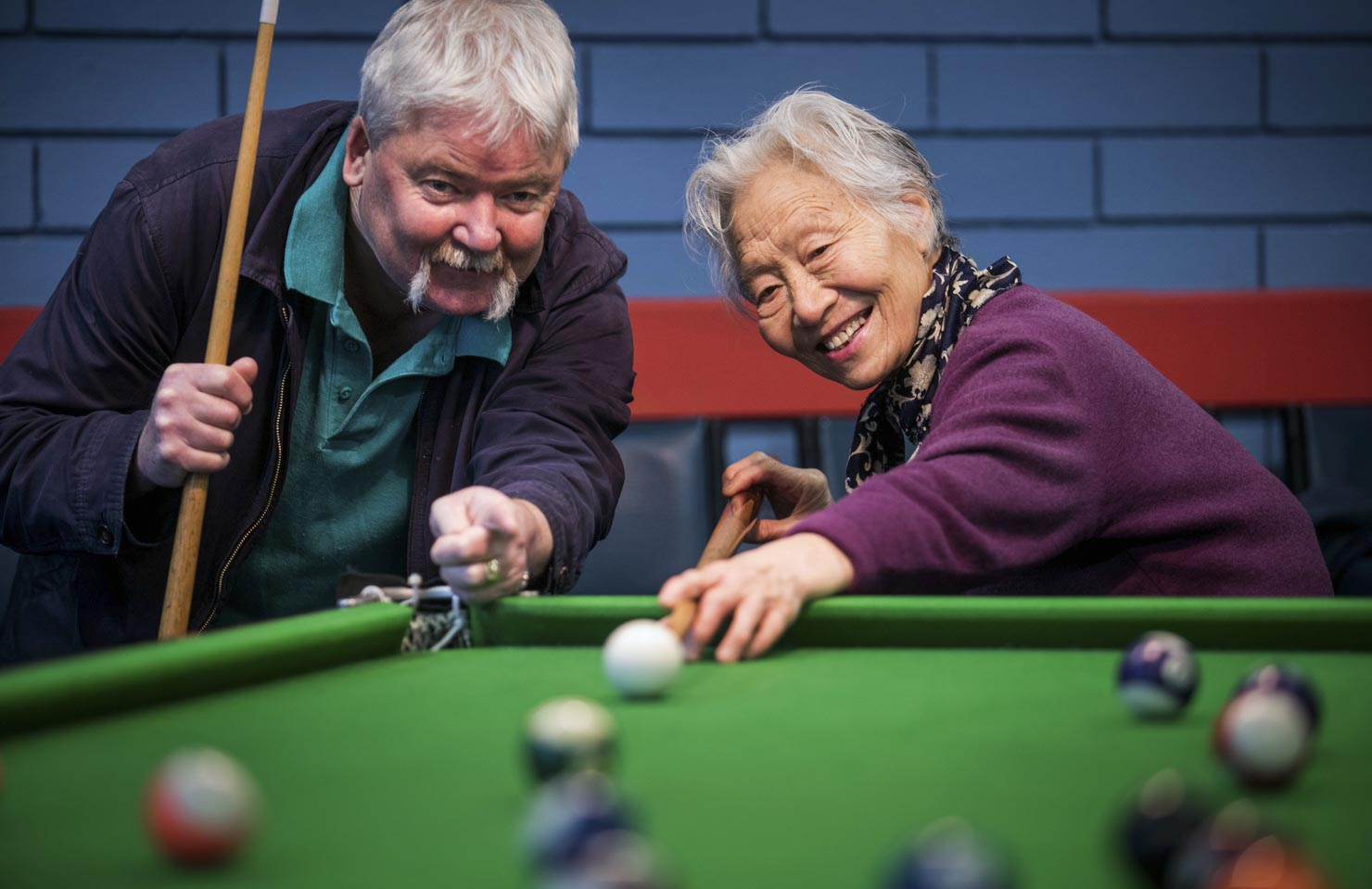An Anglo-Australian man and Vietnamese-Australian woman play billiards together