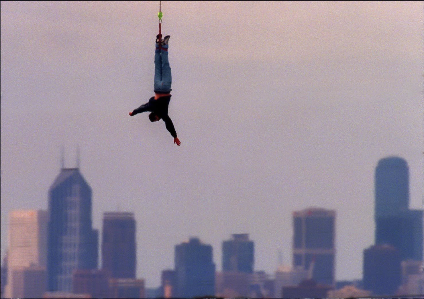 A man bunjee jumping with city backdrop