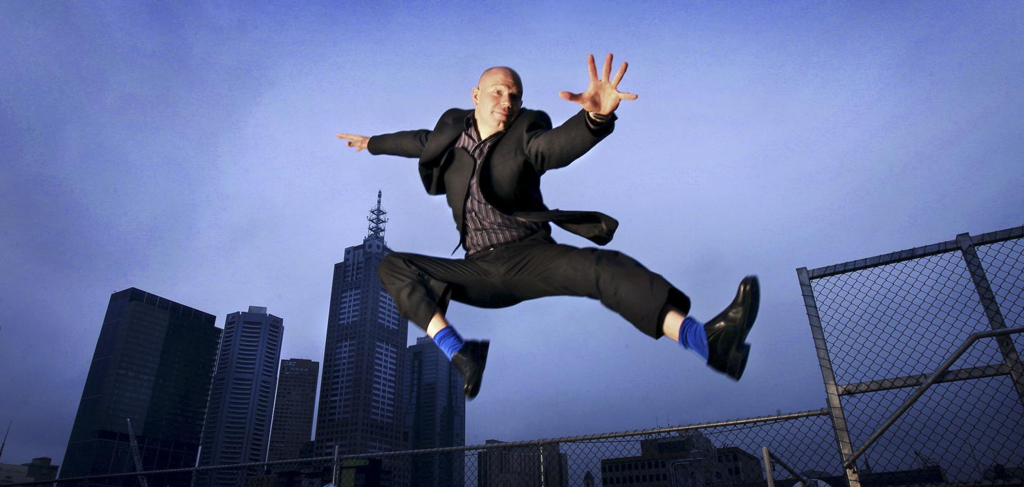 Executive leaping in front of city buildings