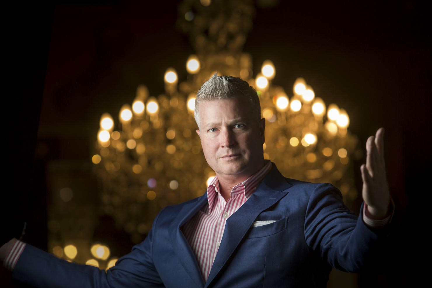 Megastar Millionaire man in front of chandelier
