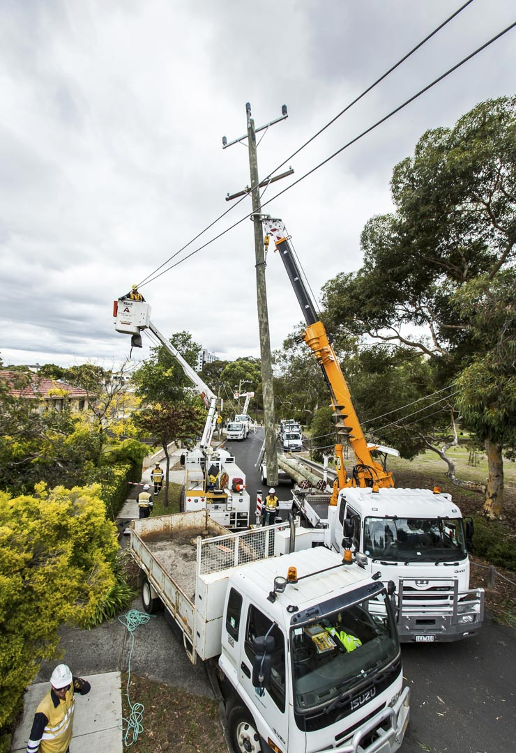 Electrical workers install electric power poles