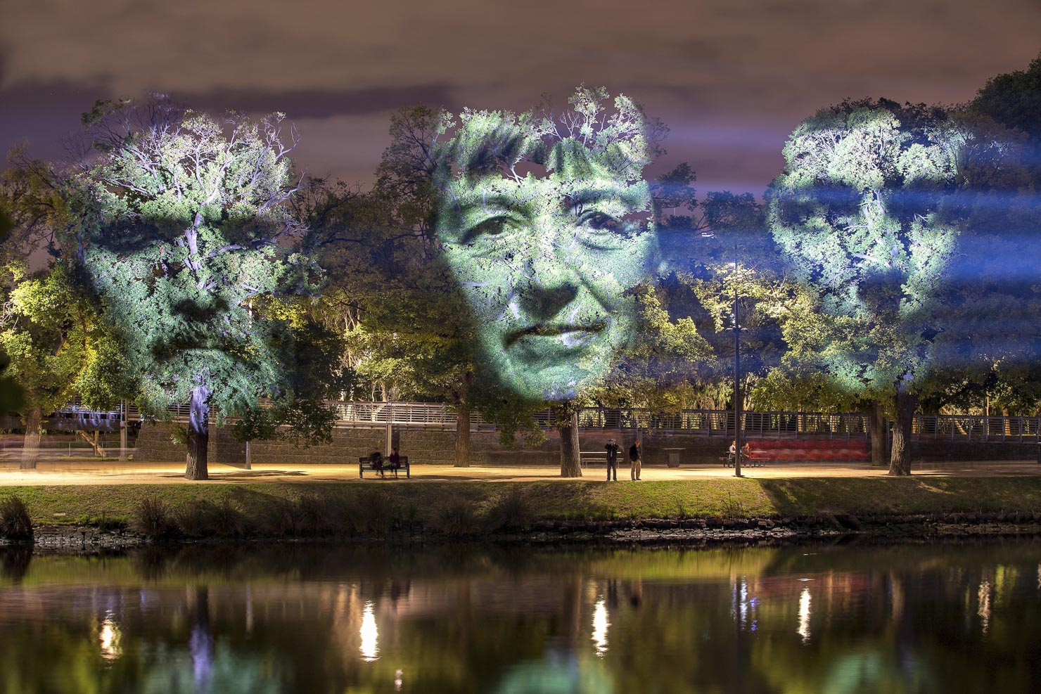 Projections of faces on park trees at a night time event