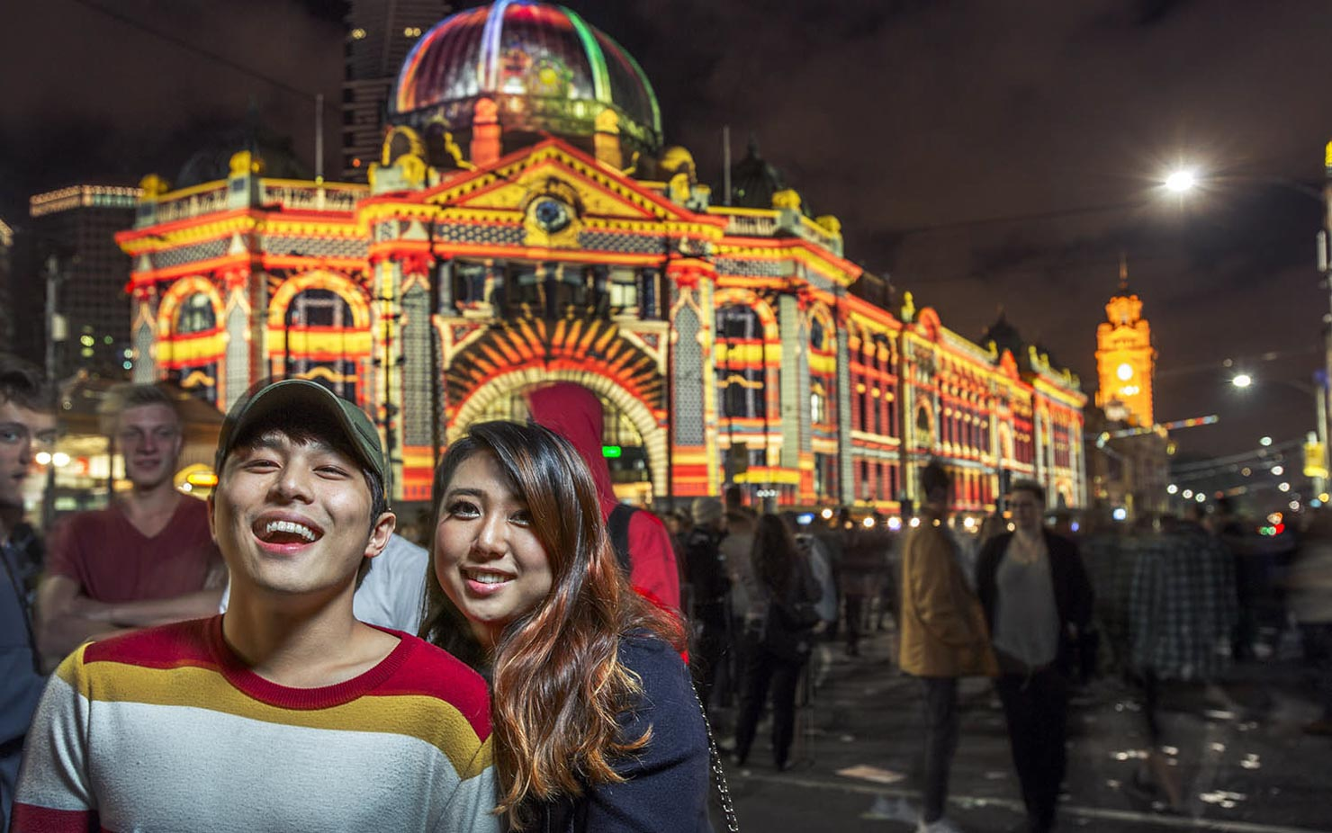 Couple outside Flinders Street Station with projections at a night time event