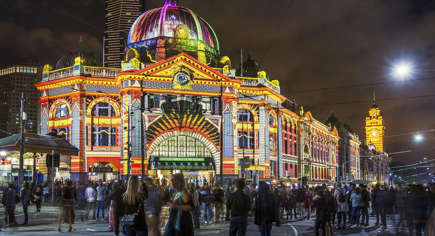 People outside Flinders Street Station with projections at a night time event
