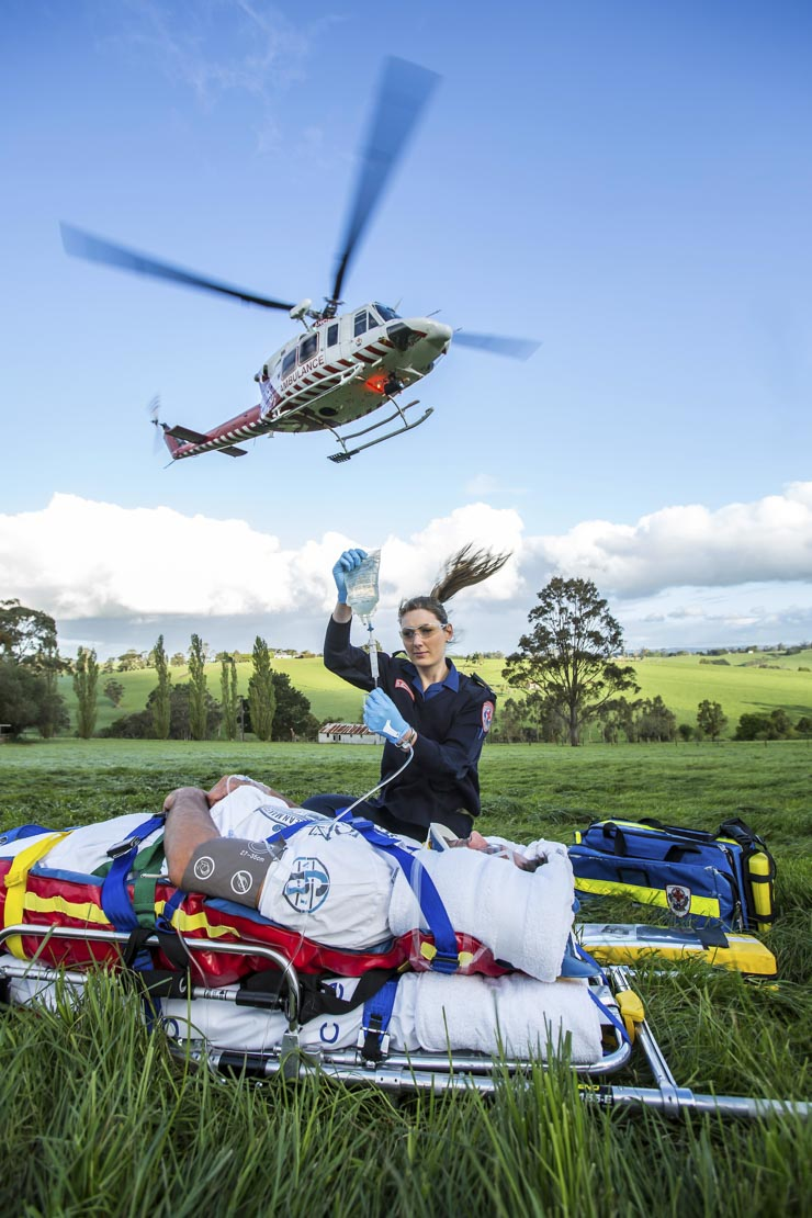 Female Ambulance Victoria paramedic works with a patient while an ambulance helicopter lands