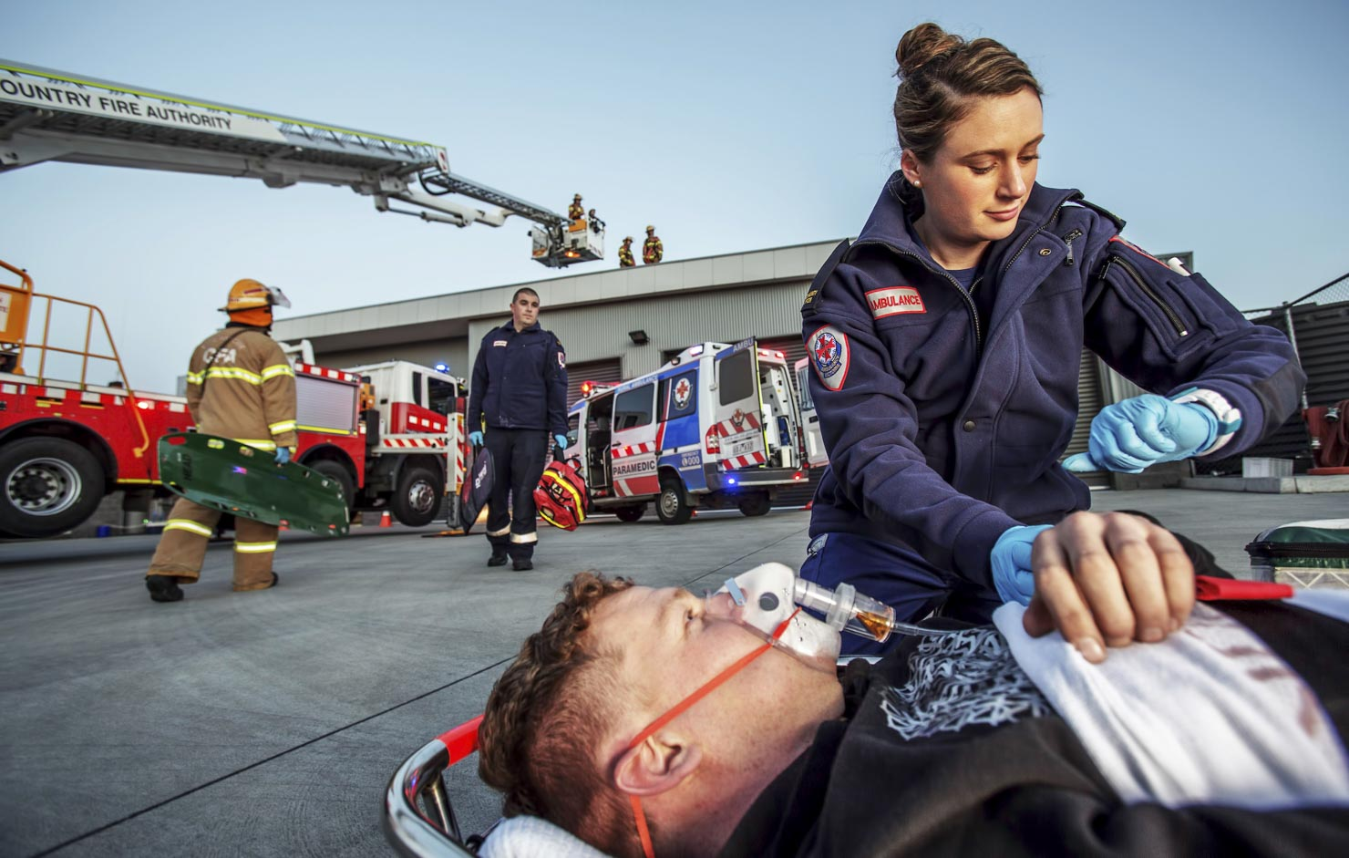 Ambulance Victoria paramedic works with a patient while fire brigade examine a roof