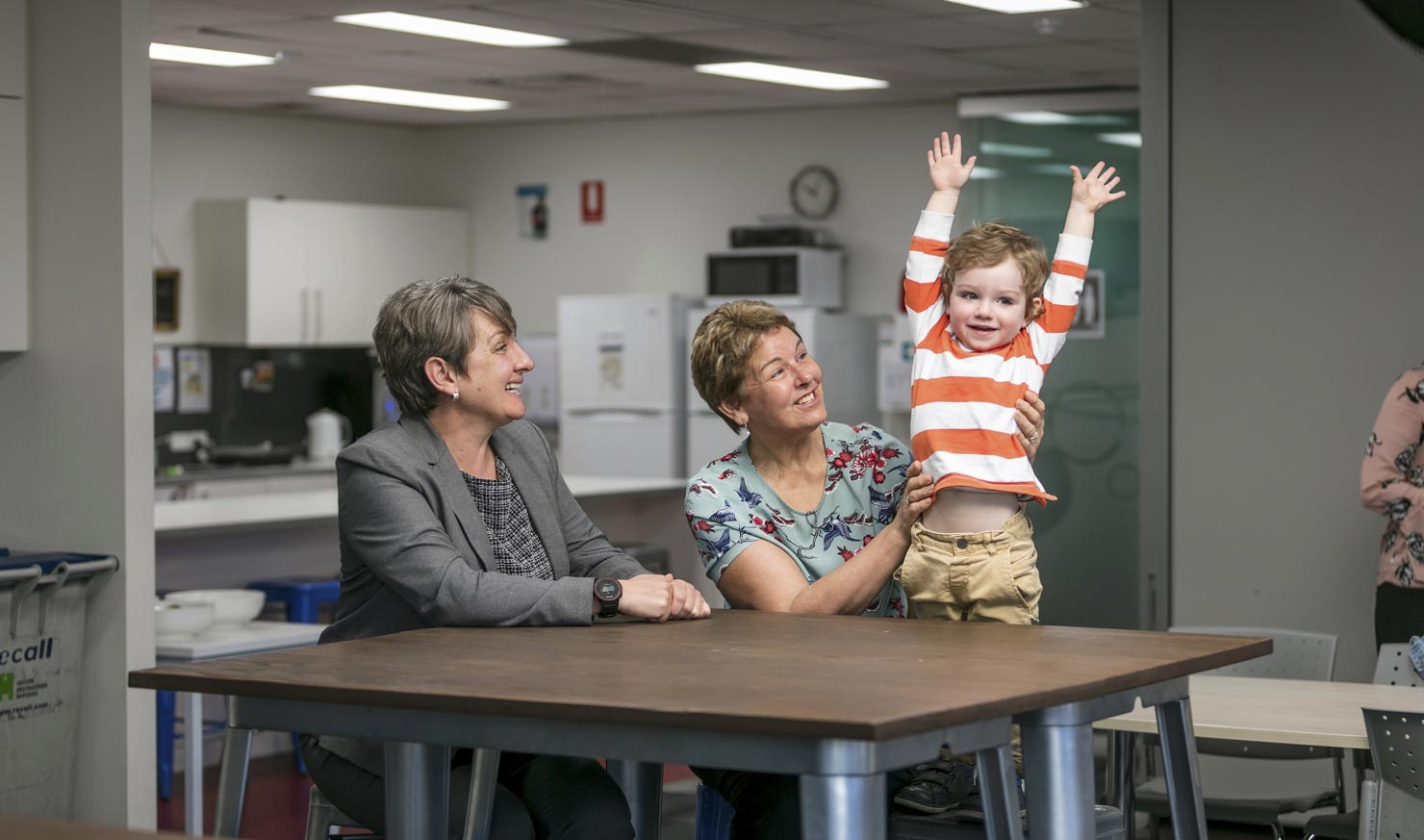 Workers entertain a child in their workplace on Bring Your Child To Work Day