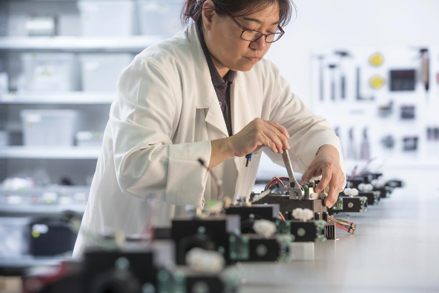 Electronics manufacturing technician working on equipment in a laboratory