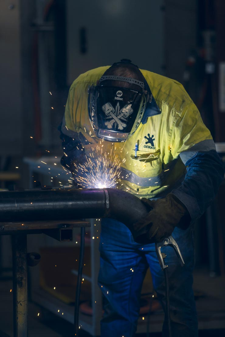 Industry worker welding a pipe at Gekko Systems