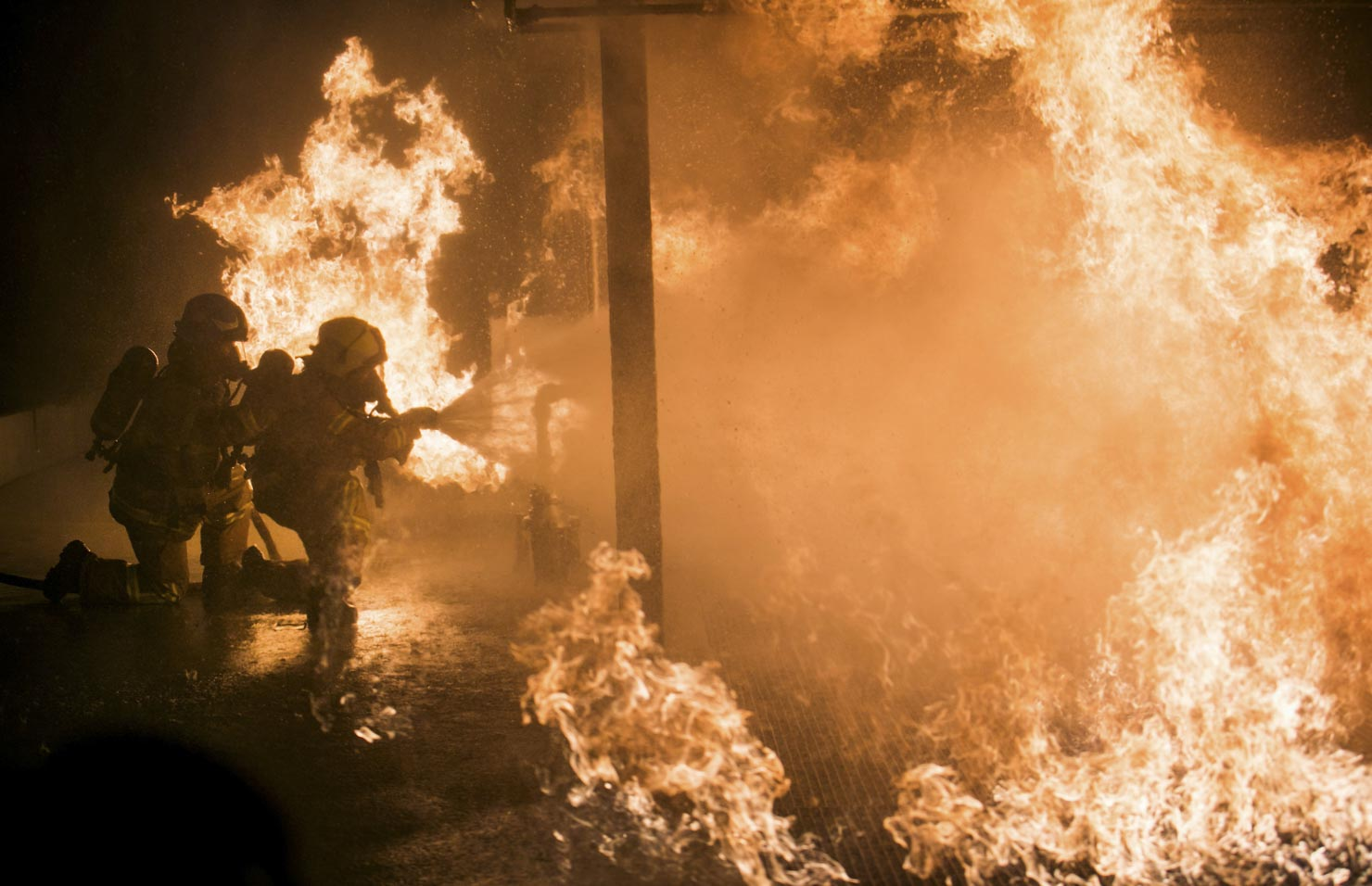 Melbourne Fire Brigade officers dowse a huge fire with a water hose